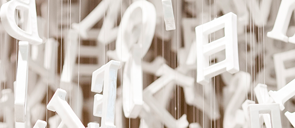 White ceramic letters hanging from fishing line.